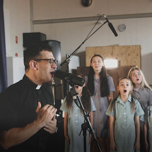 Fr Rob Galea and students Notre Dame College in Shepparton singing.