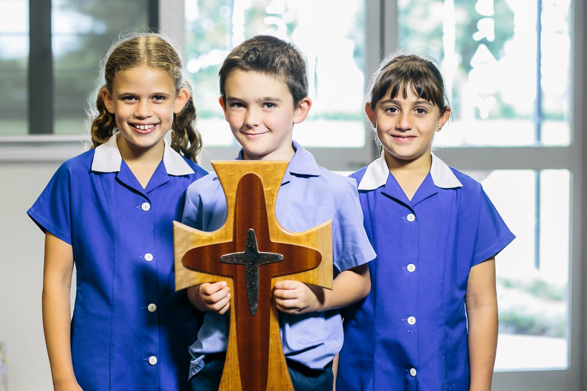 Townsville Catholic Education three students, one holding a wooden cross.