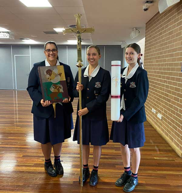 Students with a 200 years candle at St Benedict College Pennant Hills Liturgy