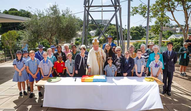 Students, Catholic education staff and leaders, and Bishop of Townsville Tim Harris DD celebrate with 200 years cake